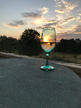 A glass of wine on the deck with the most beautiful sunsets.